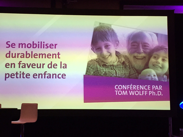 Tom Wolff Delivers | Photo of Tom and grandchildren Jonah and Liora on jumbo screen (story below) Address at Avenir D'Enfants Conference in Quebec City November 2015.